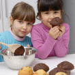 Stock Photo: Little girls cooking chocolate and vanilla cakes.