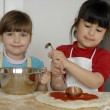 Stock Photo: Two Little girls cooking a pizza in a kitchen.Little kid in a kitchen together.