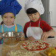 Two Little girls cooking a pizza in a kitchen.Little kid in a kitchen together. — Stock Photo #16240715
