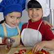 Two Little girls cooking a pizza in a kitchen.Little kid in a kitchen together. — Stock Photo #16240721