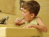Kid brushing teeth in a bathroom. — Stock Photo