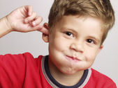 Expressive and funny kid portrait.Expression s of a little kid portrait touching ears. — Stock Photo