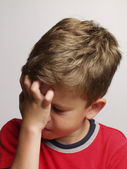 Exhausted and sad little kid portrait,rubbing his eyes — Stock Photo