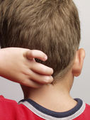 Young boy touching back of the head — Stock Photo
