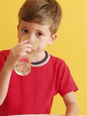 Little kid drinking a glass of water. — Stock Photo