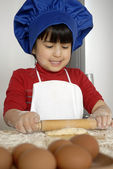 Little girl cooking a pizza in a kitchen.Little kid in a kitchen.Little girl cooking a pizza in a kitchen.Little kid in a kitchen. — Stock Photo