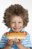 Little kid eating hot dog,Kid holding hot dog. — Stock Photo
