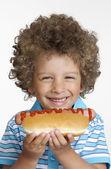 Little kid eating hot dog,Kid holding hot dog. — Stock Photo