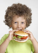 Little kid holding a big hamburger,eating hamburger. — Stock Photo