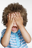 Expressive surprised kid covering his eyes. — Stock Photo