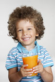 Happy little kid holding an orange juice glass,drinking orange juice. — Stock Photo