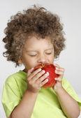 Lilla grabben håller ett rött äpple, äta äpple. — Stockfoto