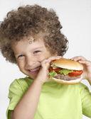 Little kid holding a big hamburger,eating hamburger. — Stock Photo