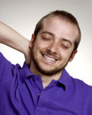 Expressive and happy young man portrait.Young man touching his neck — Stock Photo