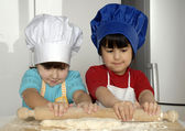 Two Little girls cooking a pizza in a kitchen.Little kid in a kitchen together. — Stock Photo