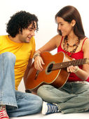 Young couple singing with a guitar — 图库照片