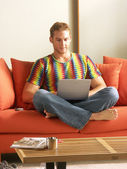 Young man using a computer at home. — Stock Photo