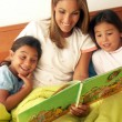 Stock Photo: Mother and daughters reading book together