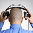 Rear view from an adult bald head man using headphones. — Stock Photo