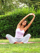 Beautiful young woman doing yoga on a patch of grass — Stock Photo