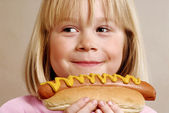 Little girl eating a hot dog — Stock Photo