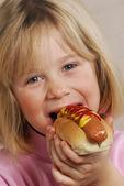 Menina comendo um cachorro-quente — Foto Stock