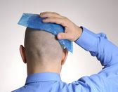 Rear view from a man holding an icepack on his head.Headache man holding ice bag. — Stock Photo