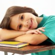 Little school girl on her desk — Stock Photo