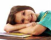 Little school girl on her desk — Stock Photo