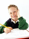 Little school kid on his desk — Stock Photo