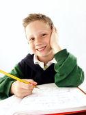Little school kid on his desk — Stock Photo