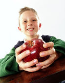 Little school kid holding a big red apple — Stock Photo
