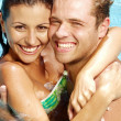 Hispanic young couple enjoying in a swimming pool. - Foto Stock