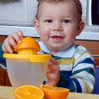 Little baby squeezing orange slices.Orange juice. - Stock Photo