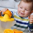 Little baby squeezing orange slices.Orange juice. — Stock Photo #19030925