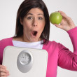 Happy slim and diet fat woman holding a weight scale and green apple. — Stock Photo