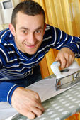 Happy young man ironing on a ironing board — Stock Photo
