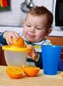Little baby squeezing orange slices.Orange juice. — Stock Photo