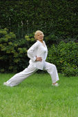 Outdoors senior woman exercising and stretching. — Stock Photo