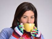 Winter woman drinking hot drink holding a yellow cup. — Stock Photo