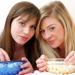 Stock Photo: Two young women eating popcorn on bed.