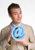 Optimistic young businessman holding an email symbol — Stock Photo