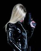Young blonde woman with black dress holding a gun. — Stock Photo