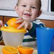 Little baby squeezing orange slices.Orange juice. — Stock Photo #23229566