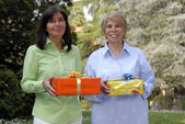 Two adult woman holding presents — Stock Photo