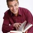 Happy young man holding and reading a book. — Stock Photo