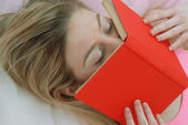 Young blonde woman reading and kissing a red book,lying down. — Stock Photo