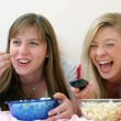 Two young women eating popcorn on bed. — Stock Photo