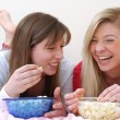 Two young women eating popcorn on bed. — Stock Photo #23279322