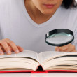 Young woman holding a magnifying glass reading a book. — Stock Photo